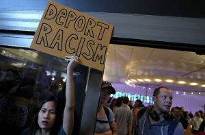 LOS ANGELES, CA - JANUARY 29:  A protester holds a sign during a demonstration against the immigration ban that was imposed by U.S. President Donald Trump at Los Angeles International Airport on January 29, 2017 in Los Angeles, California. Thousands of protesters gathered outside of the Tom Bradley International Terminal at Los Angeles International Airport to denounce the travel ban imposed by President Trump. Protests are taking place at airports across the country.  (Photo by Justin Sullivan/Getty Images)